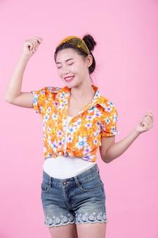Fille fashion habiller avec des gestes de la main sur un fond rose.
