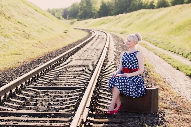 Fille fashion avec valise aux chemins de fer