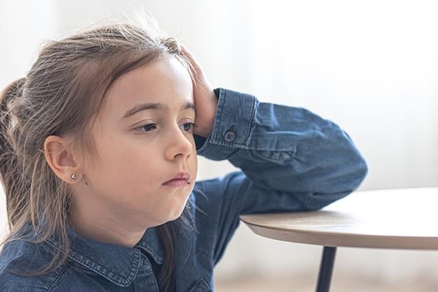 Fille fatiguée assise à la table, concept de retour à l'école.