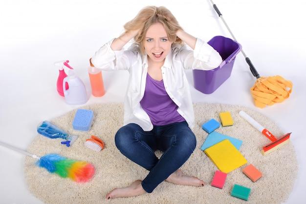 Fille fatiguée et en colère dispersée appareils de nettoyage.