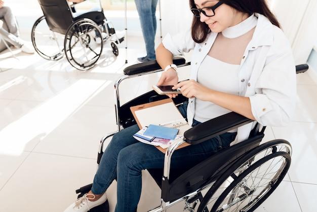 Une fille en fauteuil roulant dans le salon de l'aéroport.