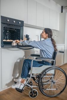 Une fille sur un fauteuil roulant ouvre un four dans la cuisine pendant la cuisson de quelque chose