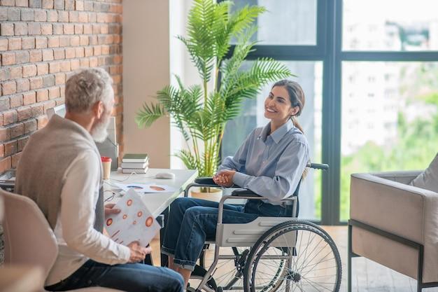 Une fille en fauteuil roulant parle à son collègue masculin et semble impliquée