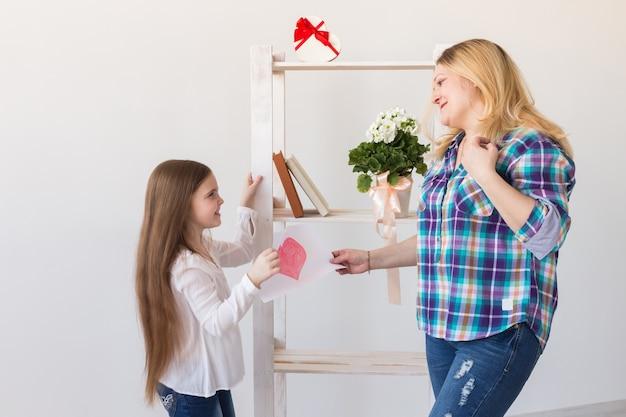 Fille félicite maman et lui donne une carte postale
