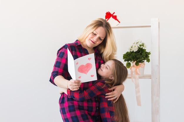 Fille félicite sa mère et lui donne une carte postale