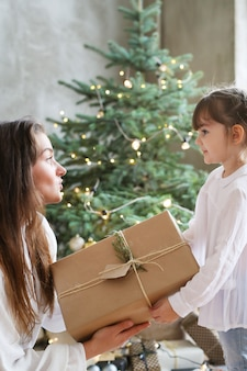 Fille et femme avec arbre de noël et cadeau