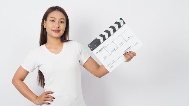 Fille ou femme asiatique tenant un clap ou une ardoise de film ou un clap et portant des bretelles. elle est utilisée dans la production vidéo, le film, le cinéma, l'industrie du cinéma sur fond blanc.