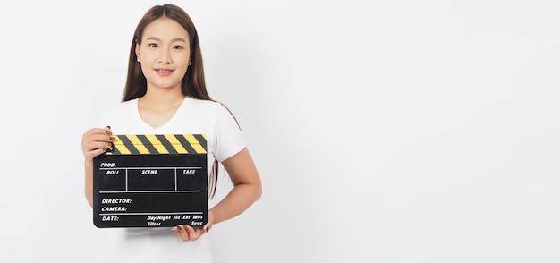 Une fille ou une femme asiatique tient un clap noir ou une ardoise de film ou un clap et porte des accolades.it utiliser dans la production vidéo, le film, le cinéma, l'industrie du cinéma sur fond blanc.