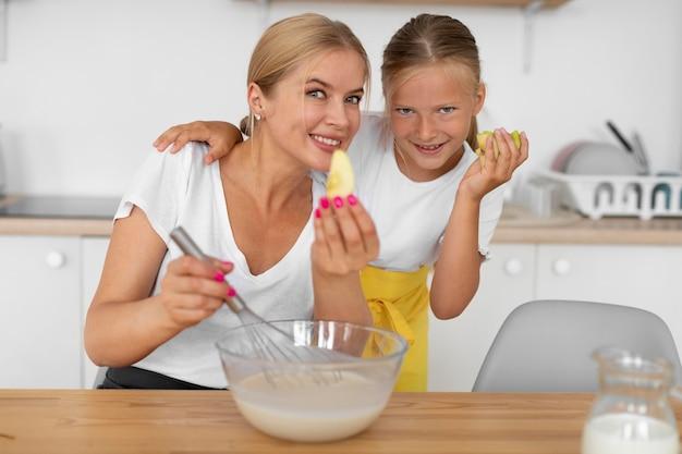 Fille et femme de coup moyen avec des fruits
