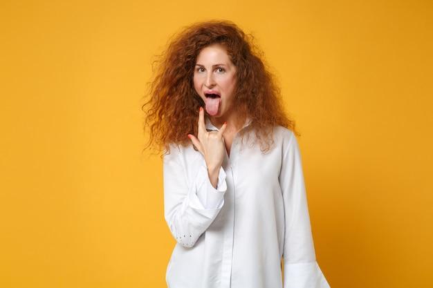 Fille de femme jeune rousse folle en chemise blanche posant isolée sur un mur orange jaune