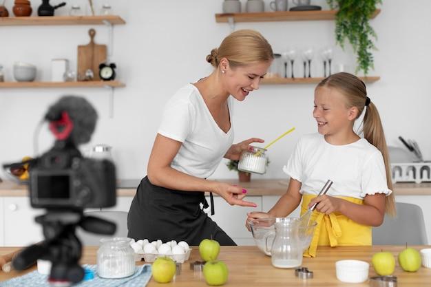 Fille et femme de plan moyen préparant la nourriture