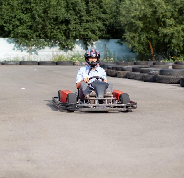 Une fille ou une femme portant un casque de sécurité fait du kart sur une piste spéciale clôturée avec des roues en caoutchouc. loisirs actifs et sports sur les transports. préparation et entraînement aux compétitions.