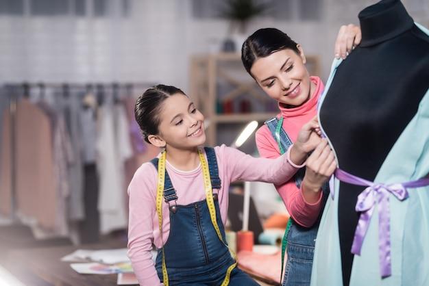 Fille et femme sont dans l'atelier de couture le soir