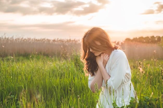 Fille ferma les yeux, priant dans un champ pendant le beau coucher de soleil