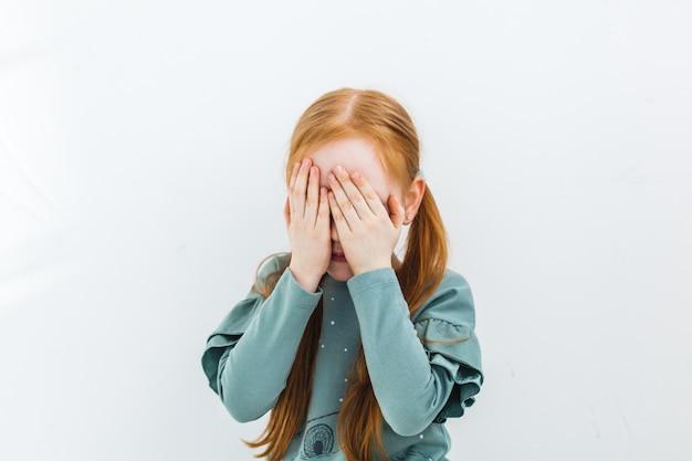 La fille ferme les yeux, se cache, pleure, triste, joue, rit