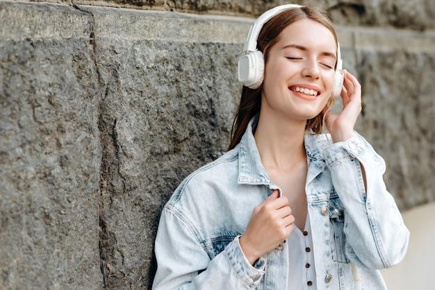 Fille fermée les yeux et écouter de la musique dans des écouteurs avec plaisir sourire en plein air