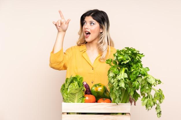 Fille de fermier adolescent avec des légumes fraîchement cueillis dans une boîte