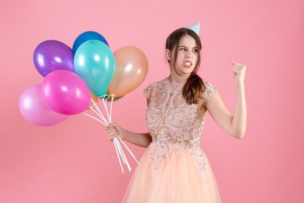 Fille de fête avec chapeau de fête tenant des ballons en colère contre quelque chose sur le rose