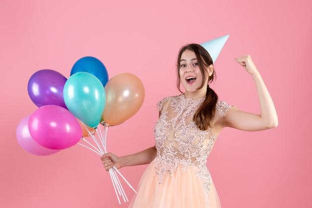 Fille de fête avec chapeau de fête tenant des ballons montrant les muscles sur rose