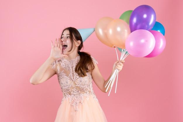 Fille de fête avec chapeau de fête tenant des ballons saluant quelqu'un sur rose