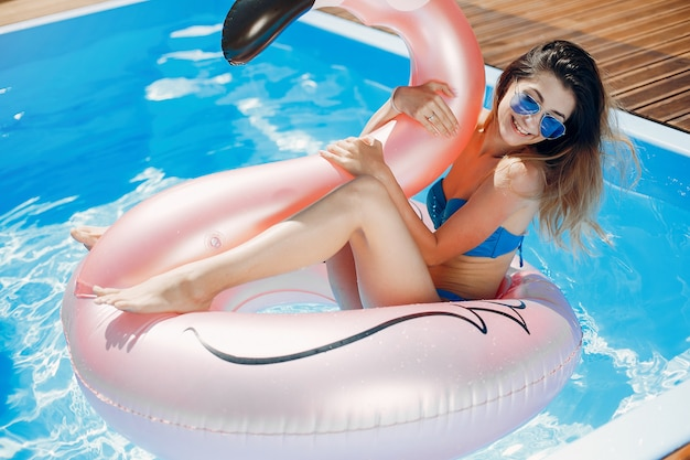 Fille à la fête de l'été dans la piscine
