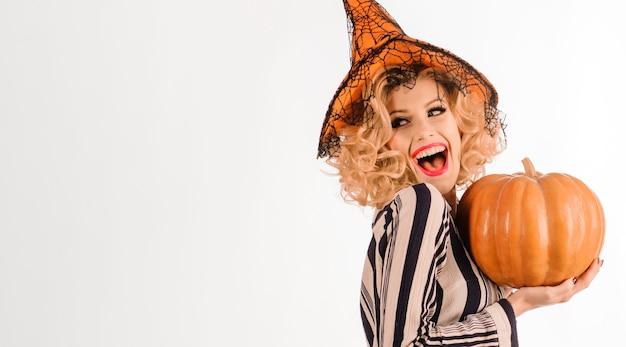 Fille de fête d'halloween. sorcière souriante avec citrouille. heureuse femme en costume d'halloween.
