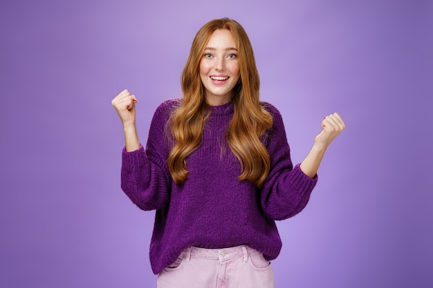 Fille fière d'elle-même faisant un effort réussi en serrant les poings levés pour célébrer et triompher en souriant largement avec une expression surprise et soulagée, gagnant, atteignant l'objectif sur fond violet.