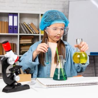 Fille avec filet à cheveux faisant des expériences scientifiques