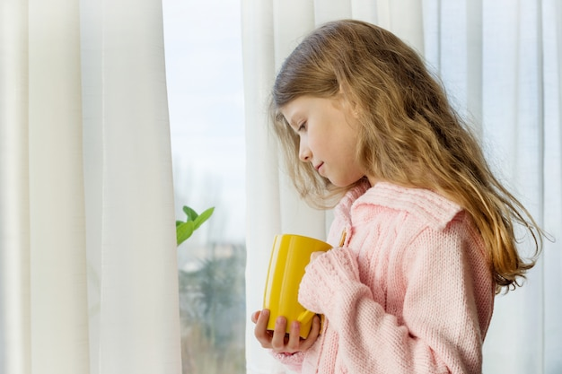 Fille fille blonde regarde dans la fenêtre