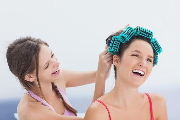 Fille fixant ses amis des rouleaux de cheveux