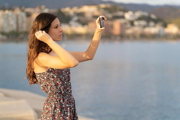 Une fille fixe ses cheveux à l'aide de l'appareil photo de son smartphone