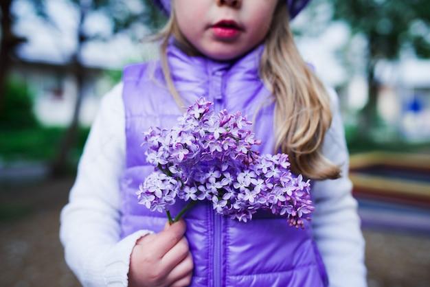 Fille avec fleur lilas en plein air