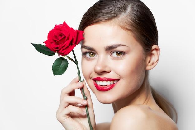 Fille avec fleur rouge sourire rose près des lèvres du visage