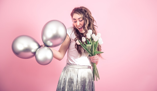 Fille avec des fleurs et des boules sur un mur coloré