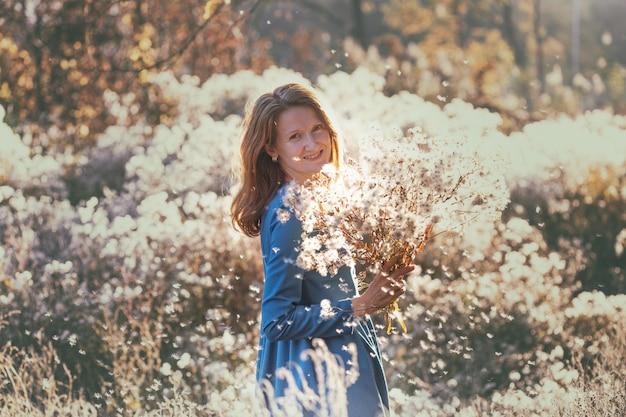 Fille avec des fleurs contre le soleil couchant dans l'après-midi d'automne. duvet de pissenlit dans le parc en automne.