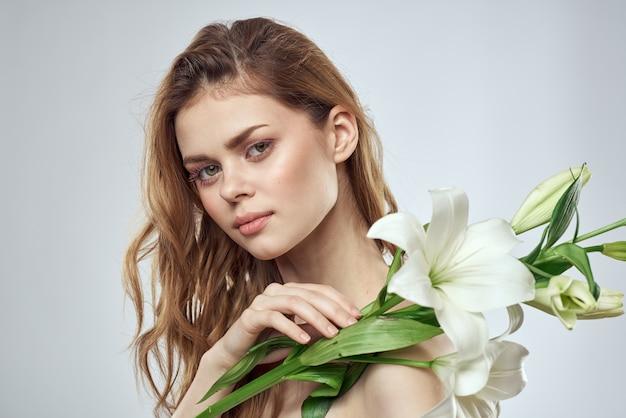 Fille avec des fleurs recadrées vue portrait gros plan printemps épaules nues peau claire maquillage.
