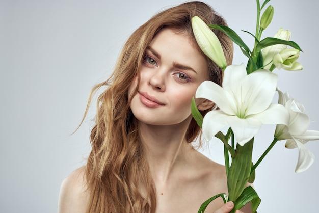 Fille avec des fleurs vue recadrée portrait close-up printemps épaules nues peau claire make up