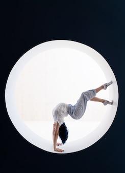 Fille flexible faisant des étirements et le poirier dans le concept de studio de mode de vie sain et de yoga