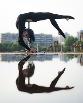 Fille flexible et en forme se pliant le dos à l'envers avec le reflet dans l'eau. concept d'individualité, de créativité et d'exception.