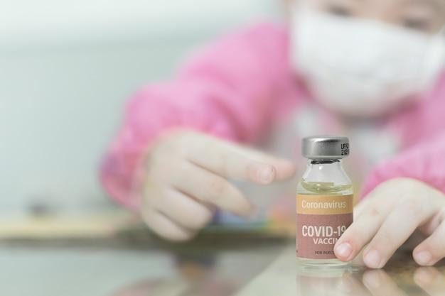 Fille floue avec masque hygiénique facial et flacon de vaccin coronavirus covid-19 à la main. contexte conceptuel pour le nouveau virus corona (nouvelle maladie coronavirus 2019, vaccin covid-19 pour les enfants.