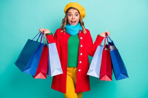 Une fille folle étonnée a impressionné 50% de réduction sur les ventes acheter tous les sacs d'exposition du centre commercial crier wow omg porter des pantalons de pull rouge vert bleu jaune pantalon couvre-chef isolé fond de couleur sarcelle