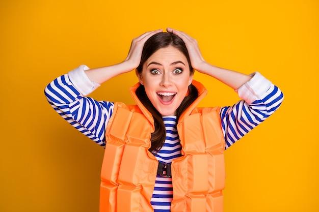 Une fille folle et positive choquée a un gilet de sauvetage impressionné important sauvetage plage travail toucher mains tête crier wow omg porter des vêtements élégants isolé brillant fond de couleur