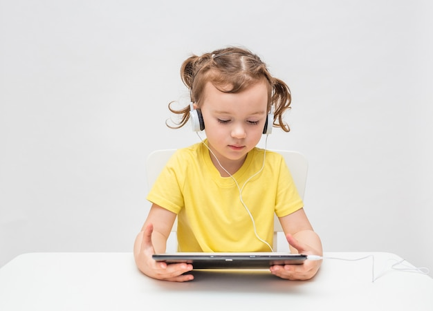 Une fille sur fond blanc dans un t-shirt jaune. la jeune fille écoute de la musique avec des écouteurs et une tablette. apprentissage à distance