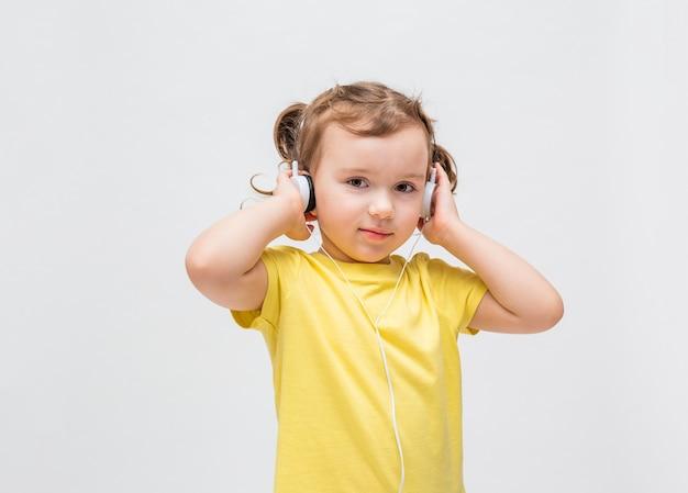 Une fille sur fond blanc dans un t-shirt jaune. la petite fille écoute de la musique avec des écouteurs.