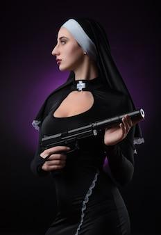 Fille sur fond noir dans une robe de nonne posant avec une arme à feu, visant, tirant