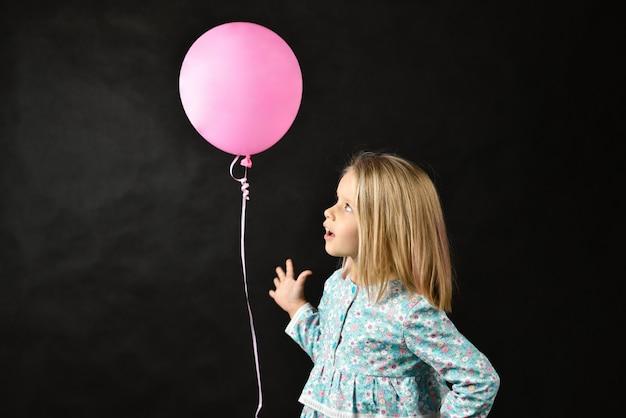 La fille sur fond noir souffle un ballon