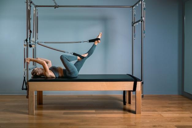 Fille de formateur de palais posant pour un réformateur dans la salle de gym. concept de remise en forme, équipement de fitness spécial, mode de vie sain, plastique. espace copie, bannière sportive pour la publicité.
