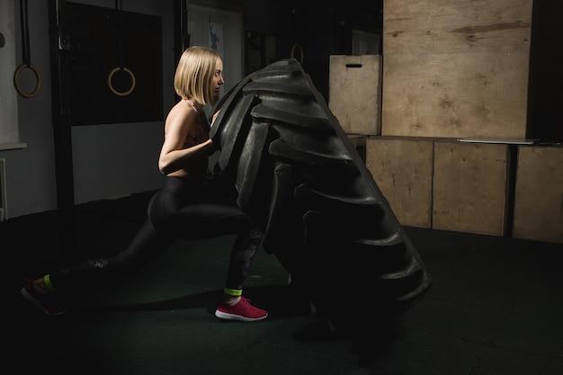Fille forte poussant un pneu dans la salle de gym.
