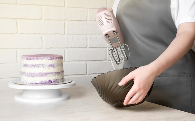 La fille fouette la crème pour le gâteau avec un mélangeur.