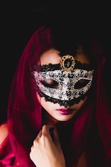 Fille avec un foulard rouge sur la tête et un masque vénitien